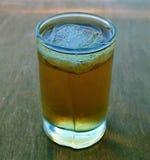 Een glas whisky met ijs, houten achtergrond Stock Foto