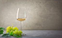 Een glas witte wijn en een bos van druiven stock fotografie