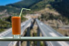 Een glas wortelsap in de koffie met mening over een snelheidsweg door het venster stock foto's
