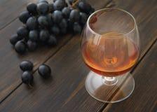 Een glascognacglas brandewijn of cognac met een bos van zwarte druiven stock foto's