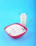 Een glashoogtepunt van suikerkubussen en een kom met suiker op een blauwe achtergrond De risico's van de dieetgezondheid hadden o Royalty-vrije Stock Foto
