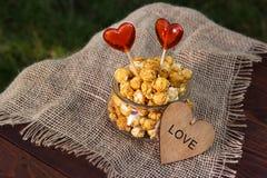 Een glaskop met gekarameliseerde popcorn en lollys op een houten lijst Gouden popcorn en een houten hart Romantisch concept Royalty-vrije Stock Afbeeldingen