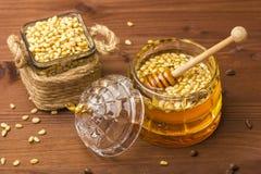Een glaskruik heerlijke honing met pijnboomnoten Bank met pijnboomnoten Royalty-vrije Stock Foto