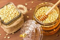 Een glaskruik heerlijke honing met pijnboomnoten Bank met pijnboomnoten Royalty-vrije Stock Afbeelding