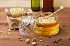 Een glaskruik heerlijke honing met pijnboomnoten Bank met pijnboomnoten Stock Fotografie