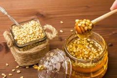 Een glaskruik heerlijke honing met pijnboomnoten Bank met pijnboomnoten Houten achtergrond Stock Afbeelding
