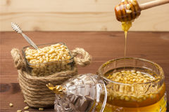 Een glaskruik heerlijke honing met pijnboomnoten Bank met pijnboomnoten Houten achtergrond Stock Foto