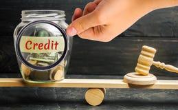 Een glaskruik met muntstukken en de inschrijving 'Krediet 'en de hamer van de rechter zijn op de schalen Schuld het herstructurer stock foto's