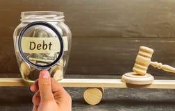 Een glaskruik met muntstukken en de inschrijving 'Schuld 'en de hamer van de rechter zijn op de schalen Concept financiële crisis royalty-vrije stock afbeelding