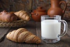 Een glasmok met melk en een vers broodje die op een oude lijst aangaande een achtergrond van baksel van tarwemeel en ceramische s Royalty-vrije Stock Fotografie