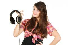 Een glimlachend gelukkig meisje houdt hoofdtelefoons in een hand Royalty-vrije Stock Foto's