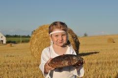 Een glimlachend gesierd meisje in slavic traditioneel chemise het houden van een brood van een roggebrood in geoogst ingediend royalty-vrije stock foto's