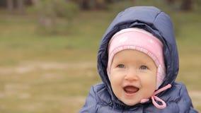 Een glimlachend meisje die een GLB en een jasje met de kap dragen stock video
