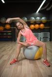 Een glimlachend meisje die geschiktheidsoefeningen doen Sportenvrouw het uitrekken zich op een geschikte bal op een gymnastiekach stock afbeelding