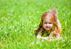 Een glimlachend meisje ligt op de weide Stock Afbeelding