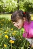Een glimlachend meisje met een vlinder stock foto's