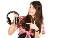 Een glimlachend meisje toont een vinger op hoofdtelefoons Royalty-vrije Stock Foto