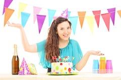 Een glimlachend verjaardagswijfje met partijhoed het stellen Stock Fotografie