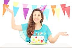 Een glimlachend verjaardagswijfje met partijhoed het stellen Stock Afbeelding