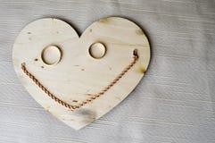 Een glimlachend, vrolijk die gezicht van een houten hart wordt gemaakt, huwelijks gouden ringen en een vrouwelijke gouden ketting stock foto's