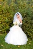 Een glimlachende gelukkige bruid met een bloemboeket Stock Afbeelding