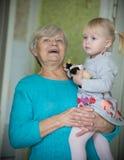Een glimlachende grootmoeder die een klein babymeisje houden royalty-vrije stock afbeelding