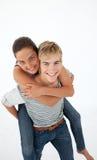 Een glimlachende jonge jongen is op zijn rug een mooie gir Stock Foto