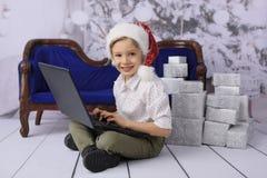 Een glimlachende jongen als Santa Claus met een Kerstboom op de achtergrond stock foto