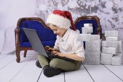 Een glimlachende jongen als Santa Claus met een Kerstboom op de achtergrond stock afbeeldingen