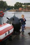 Een glimlachende jongen dichtbij een mijnwapen op het hogere dek van een oorlogsschip stock foto