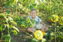 Een glimlachende jongen met een mand van zonnebloemen Glimlachende jongen met zonnebloem Een leuke glimlachende jongen op een geb royalty-vrije stock foto's