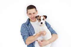 Een glimlachende knappe mens die een rashond op een witte achtergrond houden Het concept mensen en dieren jonge mens die zijn hon royalty-vrije stock fotografie