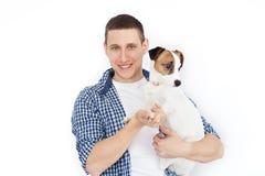 Een glimlachende knappe mens die een rashond op een witte achtergrond houden Het concept mensen en dieren jonge mens die zijn hon stock foto