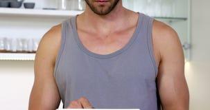 Een glimlachende mens die een mouwloos onderhemd dragen die zijn digitale tablet gebruiken stock video