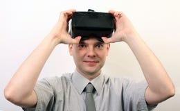 Een glimlachende mens die of op Oculus-geïmponeerde hoofdtelefoon van de Spleetvr de virtuele werkelijkheid opstijgen zetten, pos Royalty-vrije Stock Fotografie