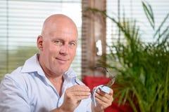 Een glimlachende oudste maakt zijn glazen schoon Royalty-vrije Stock Foto