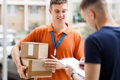 Een glimlachende persoon die een oranje T-shirt en een naamplaatje dragen levert een pakket aan een cliënt, die van hem zet royalty-vrije stock afbeelding