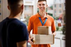 Een glimlachende persoon die een oranje T-shirt en een naamplaatje dragen levert pakketten aan een cliënt Vriendschappelijke hoge stock afbeeldingen