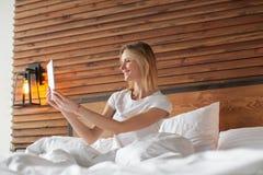 Een glimlachende vrouw ligt op bed het scrollen door haar tablet stock afbeeldingen