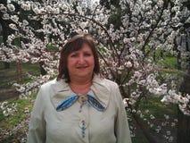 Een glimlachende vrouw op middelbare leeftijd tegen de achtergrond van een tot bloei komende abrikozenboom royalty-vrije stock fotografie