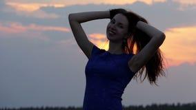 Een glimlachende vrouw stoeit en heft haar los lang haar omhoog in slo-mo op stock video