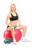 Een glimlachende vrouwelijke atleet die op een geschiktheidsbal rusten Stock Afbeelding