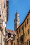 Een glimp van de bovenkant van Torre del Mangia achter Piazza del Campo in Siena royalty-vrije stock foto