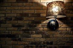 Een gloeiende lamp op een donkere bakstenen muur Een achtergrond, een bakstenen muurtextuur met een lamp Stock Fotografie