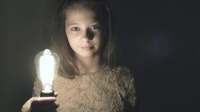 Een gloeilamp met de lichten van een wolframgloeidraad omhoog in de handen van een meisje stock video