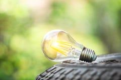 Een gloeilamp op wiel met natuurlijke verlichting en achtergrond voor sparen energieconcept Symbool van het denken of het werk su royalty-vrije stock afbeeldingen