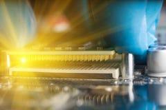Een gloved hand, die een cpu plaatsen op motherboard Macrophotographies stock foto's