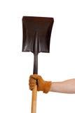 Een gloved hand die een schop houdt Royalty-vrije Stock Afbeeldingen