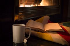 Een goed boek en een kop thee door een comfortabele brand Stock Foto