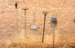 Een goed Idee om tuinhulpmiddelen op bruine muur te houden L Stock Fotografie